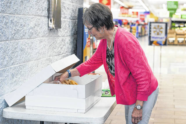 Elaine Mitchell, of Sidney, helps herself to a free doughnut at the Sidney Walmart store, Friday, June 1. The store offered the treats in celebration of National Doughnut Day.