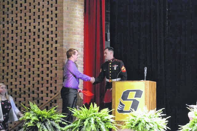 Caleb Straman, son of Kay and Alan Straman, receives the Marine Semper Fidelis Scholastic Excellence Award from Sgt. Adam Knox.