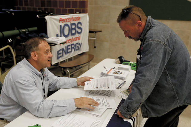FILE - In this Thursday, Nov. 2, 2017, photo, a recruiter in the shale gas industry, left, speaks with an attendee of a job fair in Cheswick, Pa.  Employers in the United States are thought to have kept up their brisk pace of hiring in June 2018, reflecting the durability of the second-longest U.S. economic expansion on record even in the face of a trade war with China. Economists have estimated that 195,000 jobs were added last month and that the unemployment rate remained at an 18-year low of 3.8 percent, according to data provider FactSet.  (AP Photo/Keith Srakocic, File)