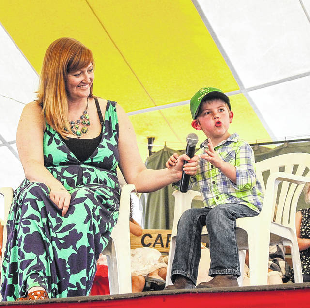 Landon Everett, 5, son of Stephanie and Tyler Everett, of Sidney, expounds about ghosts in answer to a question by mistress of ceremonies Rikki Unterbrink, left, during the 2018 Little Mister Shelby County Fair contest, Sunday, July 22.