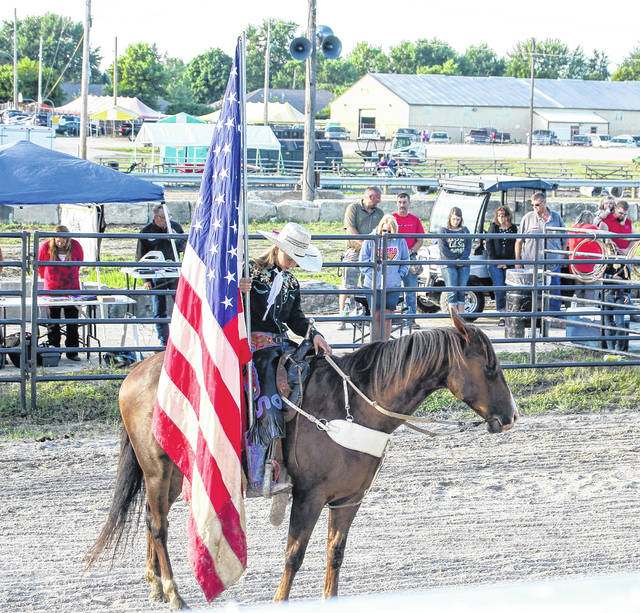 Emily Maynard, of Indiana, holds the American flag during the opening ceremony Sunday night for the Rolling Stone Rodeo at the Shelby County Fair.