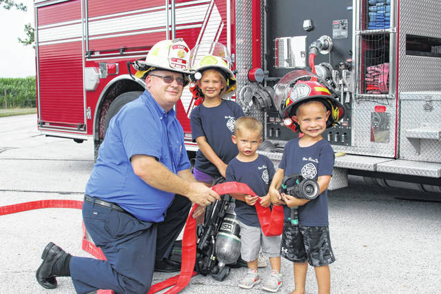 6118:  Chief Charlie Axe, left to right, with the Kettlersville Volunteer Fire Department and his grandchildren Breanna, 6, Bryson, 3, and Brennan, 4, children of Ryan and Brittany Axe of Kettlersville, pose with some of the equipment purchased with proceeds from last year's fireman's picnic. The annual picnic is a family affair and the public is invited to come and enjoy a day of fun, food, and entertainment in Kettlersville on July 21.