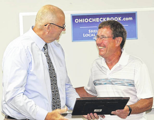 Jackson Center Mayor Scott Klopfenstein, right, presents a proclamation to village Administrator Bruce Metz, Monday, July 9. Metz was honored for winning a Seven Hats award from American Municipal Power.