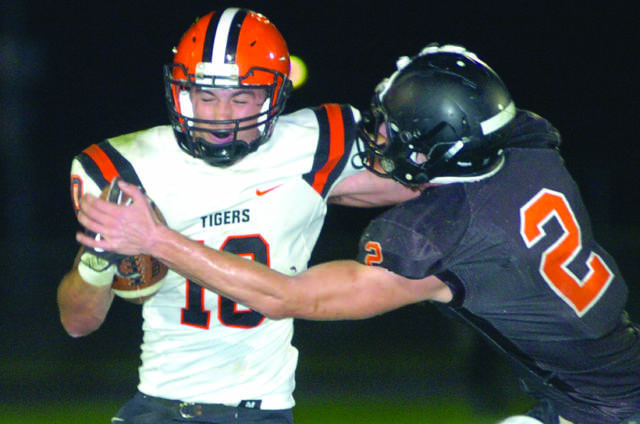 Versailles' Noah Grisez runs with pressure from a Minster defender during a MAC game on Oct. 20, 2017 in Minster. The Tigers lost 26-21, one of four losses that came by 10 points or less.