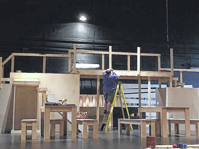 """Scenic designer Jacob Brown works on a 7-foot high bridge that is the centerpiece of the set for the Towne and Country Players' production of """"Oliver."""" The musical opens in Versailles, July 19."""