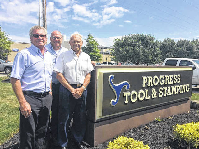 Keith, left to right, Brian and Lee Westerheide pose with the sign on their business on the occasion of the firm's 50th anniversary, Friday, July 27, in Minster.