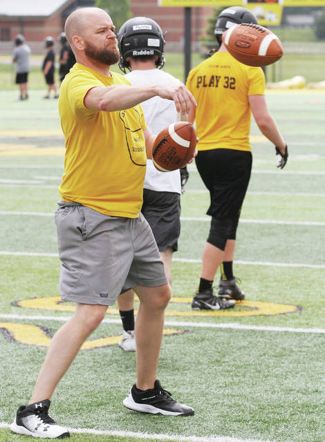 Sidney football coach Adam Doenges throws passes to players during one of the team's 10 summer practice days on June 27. Doenges is entering his eighth season as the program's head coach.
