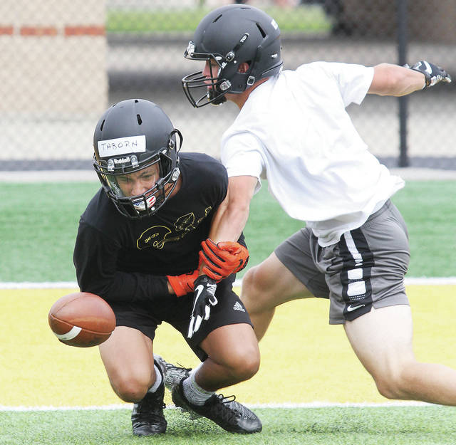 Luke Gronneberg | Sidney Daily News Sidney's Caleb Harris, right, breaks up a pass to Darren Taborn during a Sidney varsity football camp Wednesday.