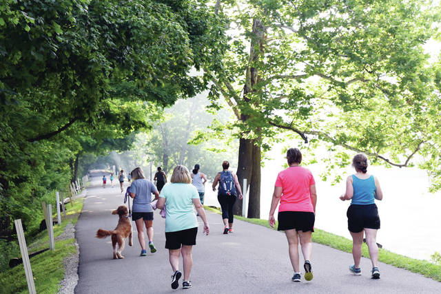 "Participants at the start of Tawawa Park's 70th anniversary ""Fun Run"" enjoy the cooler temperatures of the morning as the mist rises above Tawawa Lake Saturday, June 29."