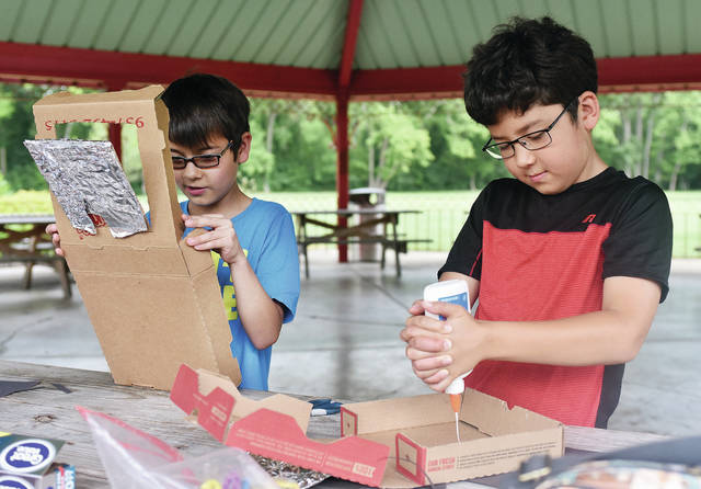 Alex Johnson, left, 9, son of Terry, and Eunju Johnson, and Bryce Monnin, 9, both of Sidney, son of Chien and David Monnin, put together solar ovens at Geib Pavilion in Tawawa Park Tuesday, July 10. The project was held by the City of Sidney Parks and Recreation Department. The solar ovens are capable of cooking food with the use of the sun. The boys weren't able to try out their ovens due to heavy cloud cover and rain.