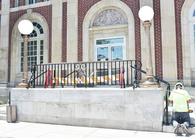 The old street lights have been reinstalled in front of the Sidney post office. Working on the post office steps is Jason Matthews, of Marion.