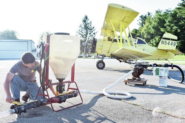 Daniel Grollimund, of Pendelton, Ind., fills his father, Dave Grollimund's, crop dusting plane with a liquid fungicide at the Sidney Airport Friday, July 13. Corn has reached a height where it must be treated from the air. The bi-plane is an AgCat with a Prettwhitney1340 600 horsepower engine. The time for air spraying is usually when corn plants begin to grow tassels.