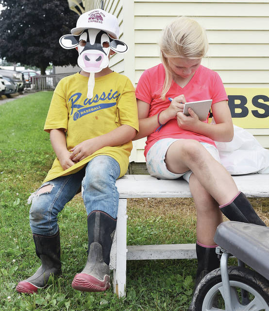 Sitting on a bench at the fair Monday, July 23 are Ignatius Schulze, left, 7, and his sister Marie Schulze, 9, both of Russia, both the children of Beth and Brent Schulze.