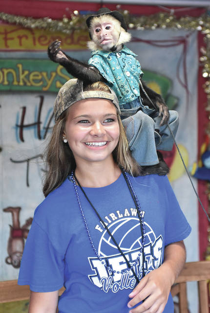 """Macie Brautigam, 14, of Plattsville, daughter of Jeff and Jennifer Brautigam, poses with a white faced capuchin name Don Juan at an organ grinder booth run by Jesse """"Monkey Man"""" Moore at the fair Monday, July 23."""