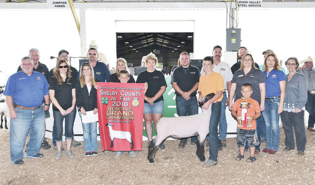 Bryson Roberts, 13, of Jackson Center, son of Dan and Shannon Roberts, member of Progressive Livestock, sells his reserve grand champion market lamb at the fair Friday, July 27.
