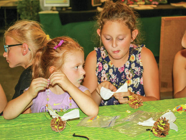 Kids making bumble bees from pine cones are McKenna Keiser, left, 4 and Kylie South, 9, both of Fort Loramie, both daughters of Matt and Jodi Keiser.