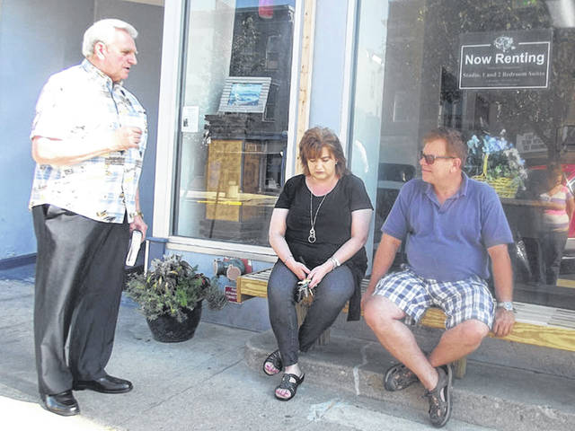 Pastor Bill Mears, of Wapakoneta, blesses a new bench built at Canal Place Apartments along Poplar Street in Sidney, recently. Seated are Penny Magos, property manager of Canal Place Apartments, and RJ Horowitz, managing member of LFR Ohio Properties, which owns the building.