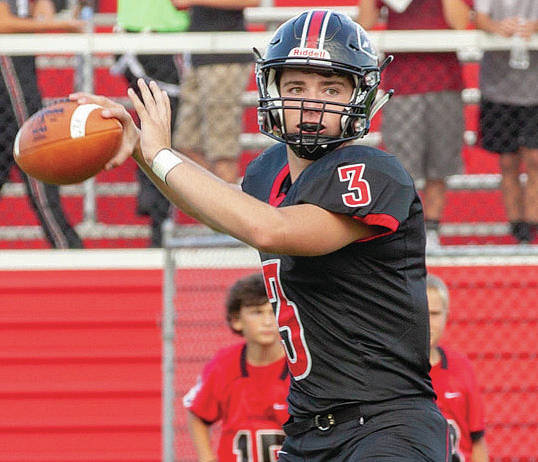 Fort Loramie's Collin Moore prepares to throw during during a nonconference game against Minster on Friday in Fort Loramie. Moore threw for 157 yards with one touchdown and one interception in the Redskins' 34-14 loss.
