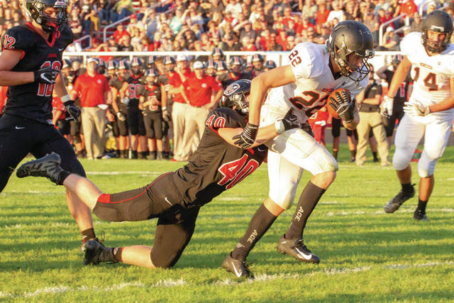Fort Loramie's Noah Guillozet grabs onto Minster's Alex Schmitmeyer during a nonconference game on Friday in Fort Loramie.