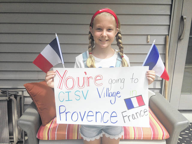 Emma Eshelman, 11, of New Bremen, holds the sign which announced she was selected for the Miami County chapter of Children's International Summer Villages (CISV) camp in France.