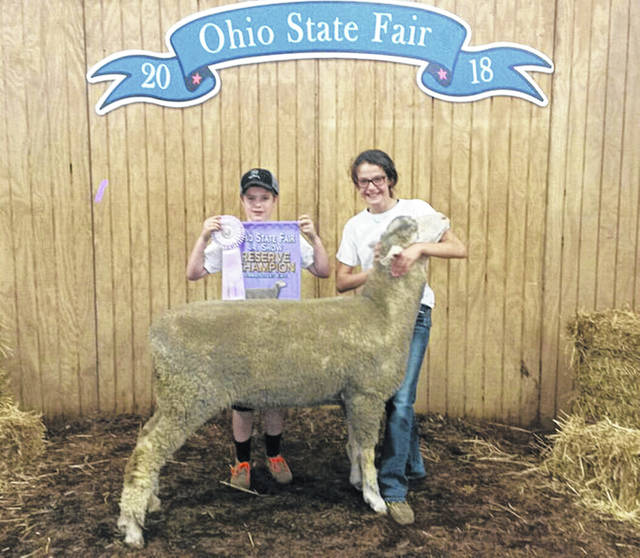 Avery Shoffner, 12, daughter of Jennir and Kevin Shoffner, of Anna, showed the reserve grand champion Rambouillet ewe at the 2018 Ohio State Fair. She is a member of Anna Livestock 4-H. Holding the banner is her brother, Carson.