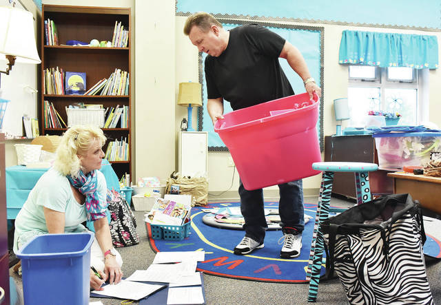 Kendi, left, and Dick Dray, set up Kendi's classroom at Christian Academy Schools in Sidney, Wednesday, Aug. 1. Dick is the new head of school and Kendi will teach kindergarten.