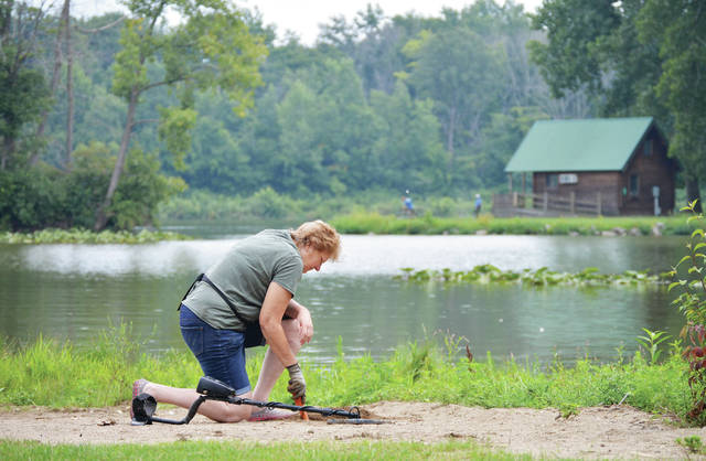 Jenny Woodworth, of West Milton, digs for treasure on a beach in Lake Loramie State Park after detecting something with her metal detector, Wednesday, Aug. 1. Woodworth had found a penny, some bottle caps and a thick, wire-shaped piece of metal.