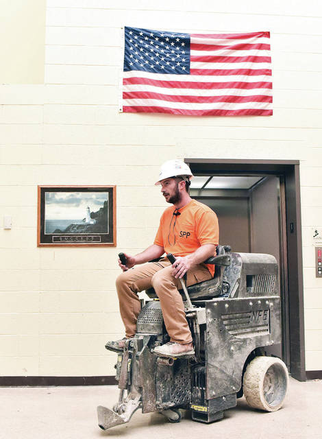 Paul Ashley, of Dayton, exits an elevator while riding a floor scraper at Anna High School, Thursday, Aug. 2. The school has been undergoing massive remodeling and will continue as the school year begins.