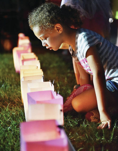 Aubrianna Webb, 5, of Anna, daughter of Carmen Webb, looks at luminaria during the 2018 Relay for Life event at the Shelby County Fairgrounds Friday, Aug. 3.