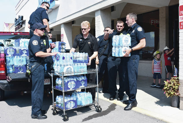 Loading up water are, left to right, Kyle Barlage, of Russia, Mitch Ahlers, of Fort Loramie, Sidney Firehouse Subs owner Tom Martin, Collin Haber, of Arcanum, and Keith Wiley, of Sidney. Holding a door open for them are brothers Lucas Brandewie, 4, and Cole Brandewie, 5, both of Houston, both children of Kyle and Melissa Brandewie. The Sidney firefighters stopped by Firehouse Subs to pickup bottled water donated in exchange for free subs. Firehouse Subs collected 184 cases of water to donate to Sidney firefighters.