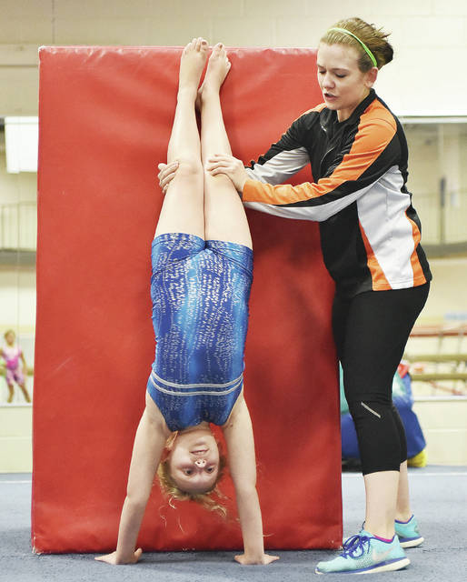 Destiny Howard, left, 9, daughter of Kris Howard and Jeff Howard, gets some help practicing her hand stand from YMCA trainer Jessica Taylor, both of Sidney, in the YMCA Kinetics Gym Wednesday, Aug. 8.