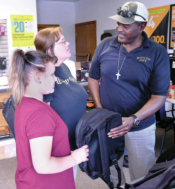Dock Henry Foy, far right, chats with Amie Baker, center, guardian of Abigale Teets, 11, all of Sidney, who will be attending Sidney Middle School, as Abigale receives a backpack and school supplies from Foy. Foy was handing out free school supplies at his Wireless Dock Store Friday, Aug. 10.