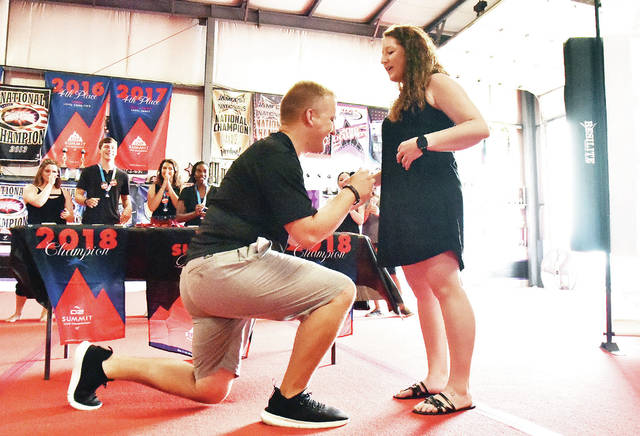 Dane Mansfield, left, proposes to his girlfriend Abbey Kramer, both of Shawnee, at the end of a ring presentation to the members of Kramer's United Tumbling Academy national championship team Sunday, Aug. 26.