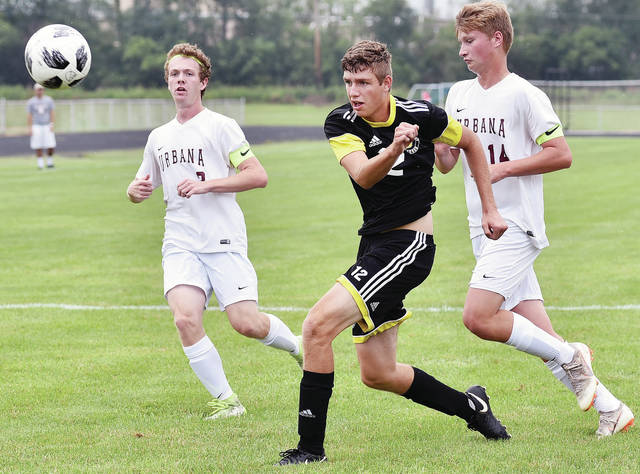 Sidney's Trey Werntz, right, kicks the ball as Urbana's Michael Trudo, left, and Ethan Burnside chase during a nonconference match on Saturday in Sidney. The Yellow Jackets won 5-4.