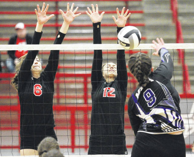 Fort Loramie's McKenzie Hoelscher, left to right, and Chloe Stang go for a block in a Division IV district final match against Miami Valley Christian Academy on Oct. 28, 2017 at Trojan Activities Center in Troy. Hoelscher and Stang are two of four returning starters for the Redskins.