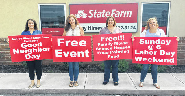 Ashley Himes, Mary Beth Reese, Ginger Reck, and Jessica Hammaker hold signs to advertise the upcoming State Farm Good Neighbor Day event.