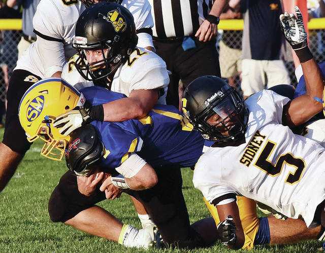 Sidney's Christian Townsend, left, and Josiah Hudgins help bring down a St. Marys runner during a nonconference game on Aug. 24. The Yellow Jackets will take on their third straight opponent with a run-oriented offense on Friday in Belmont.