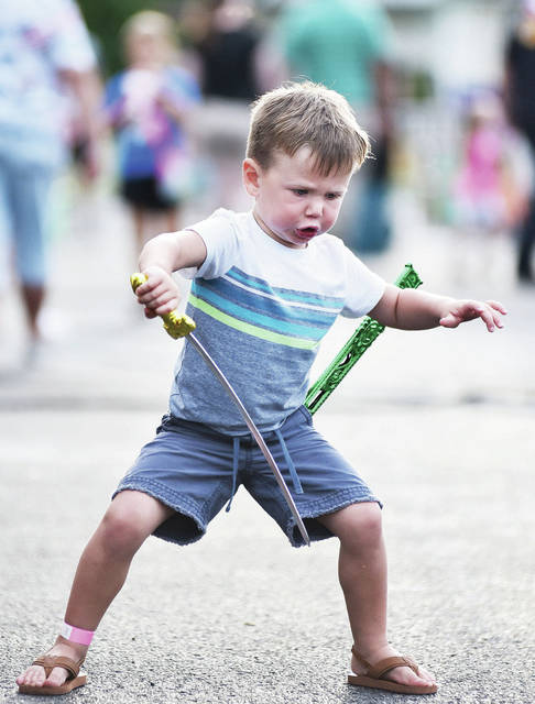 Simon Goubeaux, 2, of Russia, son of Ashley and Travis Goubeaux, plays with his newly won sword at the Russia Homecoming Festival Saturday, Sept. 1.