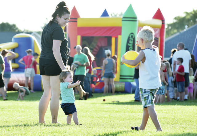 Courtney Reed, left to right, holds the hand of her daughter Aubree Reed, 1, as Benjamin Miller, 4, all of Russia, son of Karen Miller, walks towards them with a ball during Ashley Himes' State Farm Community Day at the Sidney Auto Vue Drive In Sunday, Sept. 2. Free bounce houses, face painting and a movie were provided at the Labor Day weekend event.