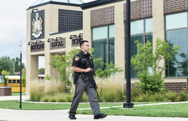 Shelby County Sheriff's Deputy Josh Spicer guards Botkins Local School while one last robber is searched for in Botkins Wednesday, Sept. 12. Spicer is the school's resource officer.