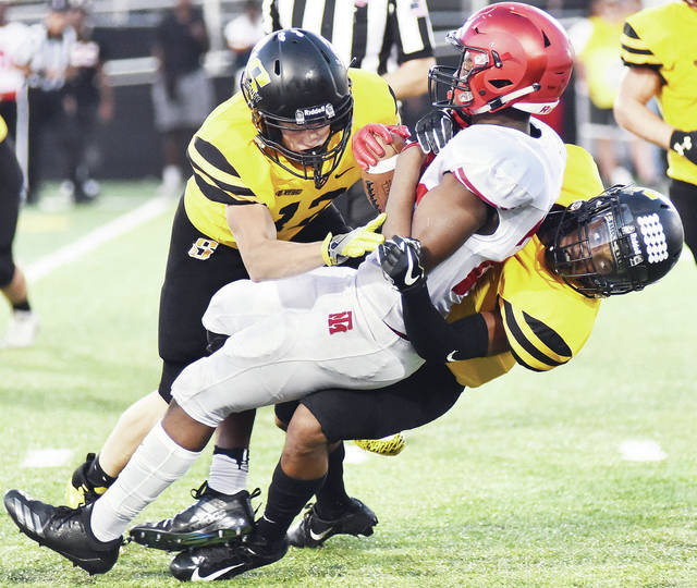 Sidney senior linebacker Landon Johnson and senior defensive back Josiah Hudgins bring down Trotwood's Daevontay Latimer during a Greater Western Ohio Conference crossover game at Sidney Memorial Stadium on Friday.