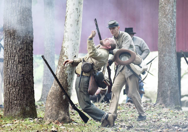 A Confederate soldier drops to the ground after being shot during a Civil War re-enactment battle at Tawawa Park Saturday, Sept. 17.