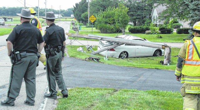 Shelby County Deputies and Sidney Firefighters standby while a DP&L worker turns off power to powerlines connected to a pole that was struck Friday, Sept. 7, around 12:45 p.m. in the front yard of 2355 Schenk Road by an eastbound white Honda Civic. As a result of the one-vehicle crash, the utility pole split and fell on the rear of the car. The female driver was the only person in the vehicle at the time of the crash. She was transported to the hospital by Sidney Rescue Squad.