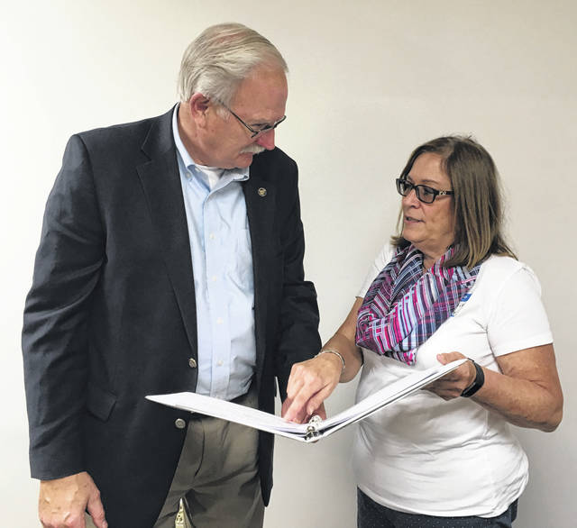 Sidney Mayor Mike Barhorst and Sidney Arborist Joyce Reier review the presentation they gave Wednesday, Sept. 26, at the Southwest Ohio Urban Forestry Conference in Cincinnati.