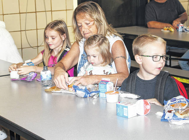 Alexis Vondenhouvel, 7, daughter of Meranda Amerine and James Vondenhouvel, of Sidney, Teresa Fogt, of Sidney, who is holding Ameria Marlow, 2, daughter of Joey and Stephanie Marlow, of Sidney, and Cole Allsup, 7, son of Valerie and Josh Conasger, of Sidney, enjoy breakfast at Emerson Elementary School. Fogt was having breakfast with her grandkids for Grandparents Day at the school on Tuesday, Oct. 9.